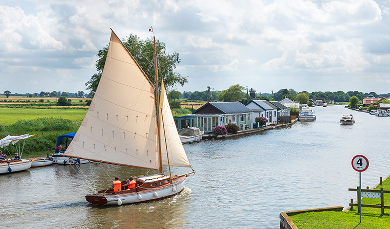 Photograph of wooden yacht sailing near Potter Heigham on the River Thurne, Norfolk Broads National Park