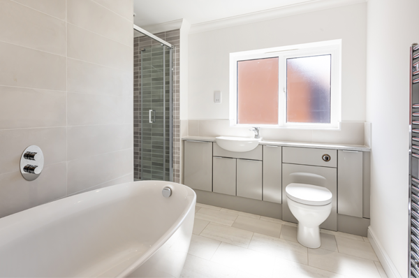 Photograph of bathroom with luxury oval bath, built in shower cubicle and fitted units with integrated sink and toilet