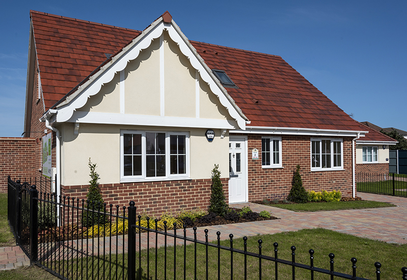 New build bungalow with blue skies, planted front garden and black metal railing fence