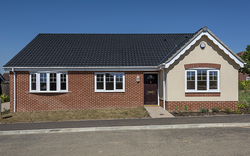 New build bungalow with blue skies and planted front garden