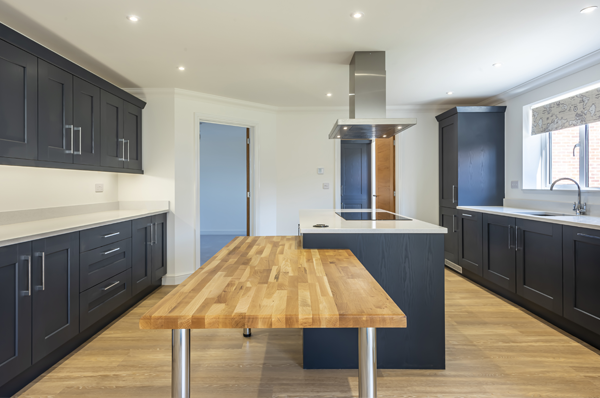 Photograph of open plan kitched with dark grey units, centre island, white worktops and wood laminate floor