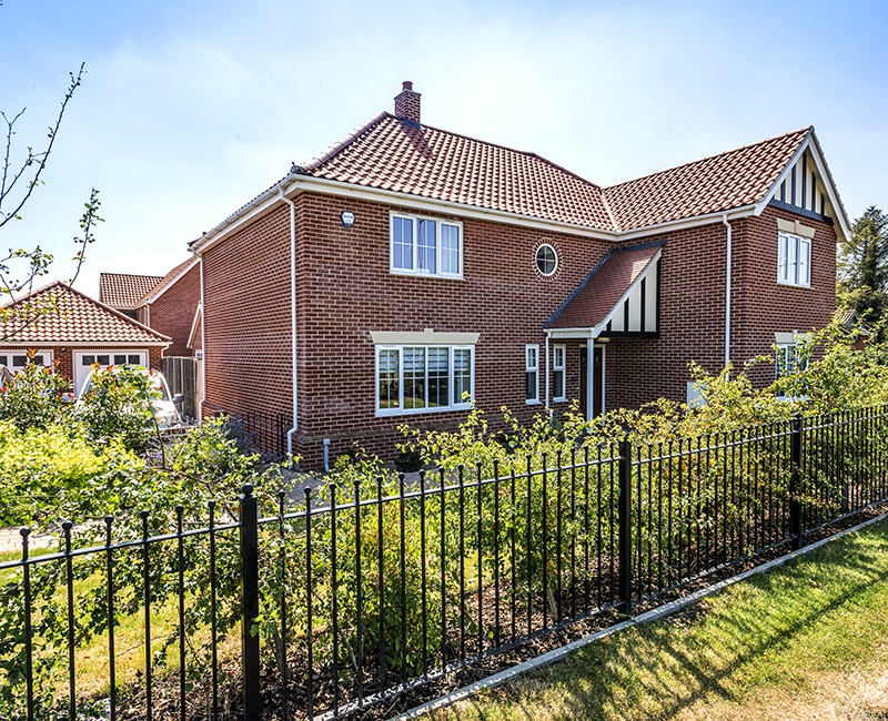 Badger Building new build house with well planted front garden and black metal railing fence